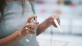 Feche acima das mãos do perfume do pulverizador da menina no verificador na loja cosmética, movimento lento vídeos de arquivo