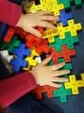 Feche acima das mãos do ` s da criança que jogam com os tijolos plásticos coloridos na tabela Fotos de Stock Royalty Free