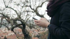Feche acima das mãos do ` s da mulher usando Smartphone que senta-se no banco no parque Menina europeia bonita que texting no tel Foto de Stock
