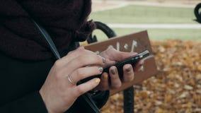 Feche acima das mãos do ` s da mulher usando Smartphone que senta-se no banco no parque Menina europeia bonita que texting no tel Foto de Stock Royalty Free