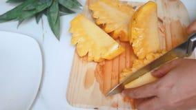 Feche acima das mãos do tiro das mulheres que usam a faca de cozinha a cortar e a descascar a profundidade do abacaxi maduro de c filme