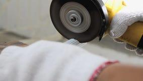 Feche acima das mãos do tiro do homem que usa o moedor bonde a cortar a tubulação de alumínio branca video estoque