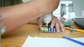 Feche acima das mãos do tiro do homem do mecânico que usa a chave de fenda elétrica para girar o parafuso na placa de circuito el vídeos de arquivo