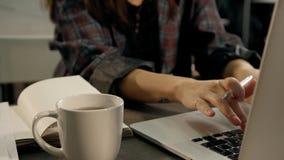 Feche acima das mãos do trabalhador de escritório fêmea que datilografa no teclado de laptop vídeos de arquivo
