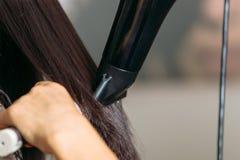 Feche acima das mãos dos cabeleireiro que secam o cabelo preto longo com secador do sopro e a escova redonda fotografia de stock