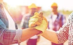 Feche acima das mãos dos construtores que fazem o aperto de mão fotos de stock royalty free