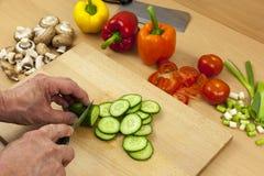 Feche acima das mãos dos cozinheiros chefe que cortam um pepino inglês Foto de Stock Royalty Free