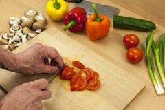 Feche acima das mãos dos cozinheiros chefe que cortam um tomate da salada Fotografia de Stock