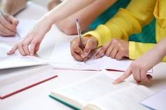 Feche acima das mãos dos estudantes que escrevem aos cadernos Foto de Stock
