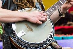 Feche acima das mãos dos jogadores de um banjo que jogam o banjo em um mercado dos fazendeiros Imagens de Stock