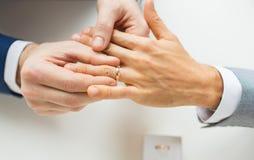 Feche acima das mãos e da aliança de casamento alegres masculinas dos pares Fotos de Stock Royalty Free