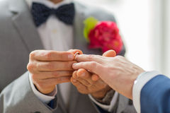 Feche acima das mãos e da aliança de casamento alegres masculinas dos pares fotografia de stock