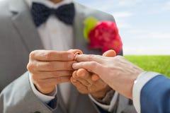 Feche acima das mãos e da aliança de casamento alegres masculinas dos pares Fotografia de Stock Royalty Free