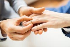 Feche acima das mãos e da aliança de casamento alegres masculinas dos pares foto de stock royalty free