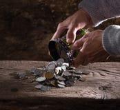 Feche acima das mãos e da pilha do ancião caucasiano de moedas velhas Fotografia de Stock