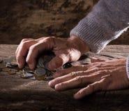 Feche acima das mãos e da pilha do ancião caucasiano de moedas velhas Imagem de Stock Royalty Free