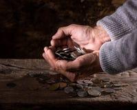 Feche acima das mãos e da pilha do ancião caucasiano de moedas velhas Imagens de Stock