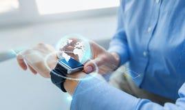 Feche acima das mãos e do holograma do globo no smartwatch imagens de stock