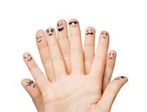Feche acima das mãos e dos dedos com caras do smiley Foto de Stock