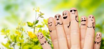 Feche acima das mãos e dos dedos com caras do smiley Imagens de Stock Royalty Free