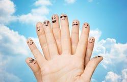 Feche acima das mãos e dos dedos com caras do smiley Imagem de Stock Royalty Free