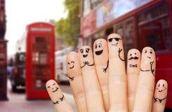 Feche acima das mãos e dos dedos com caras do smiley Fotos de Stock