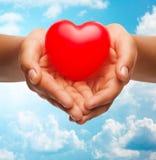 Feche acima das mãos fêmeas que guardam o coração vermelho pequeno Foto de Stock Royalty Free