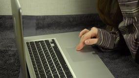Feche acima das mãos fêmeas usando o portátil que encontra-se no assoalho em casa, movimento lento video estoque