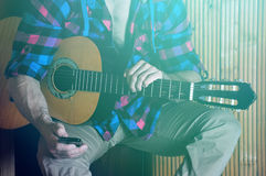 Feche acima das mãos fortes do moderno humano que guardam o telefone e a guitarra velha Imagem de Stock Royalty Free
