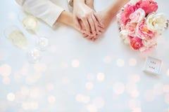 Feche acima das mãos lésbicas e das alianças de casamento dos pares imagens de stock royalty free