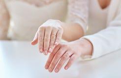 Feche acima das mãos lésbicas e das alianças de casamento dos pares Fotografia de Stock Royalty Free