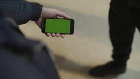 Feche acima das mãos masculinas novas que guardam o smartphone moderno com tela táctil verde A mão do ` s do homem mostra o smart fotografia de stock