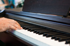 Feche acima das mãos masculinas que jogam o piano. Imagem de Stock
