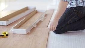 Feche acima das mãos masculinas que medem o revestimento de madeira filme
