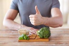 Feche acima das mãos masculinas que mostram ricos do alimento na fibra Fotografia de Stock