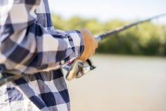Feche acima das mãos masculinas que travam peixes com giro no banco de rio f fotos de stock royalty free