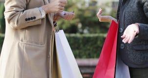 Feche acima das mãos das mulheres com sacos de compras coloridos video estoque