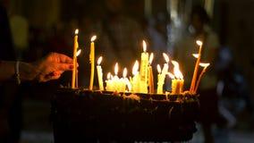 Feche acima das mãos das orações que leve velas na igreja santamente do sepulcro no Jerusalém foto de stock