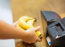 Feche acima das mãos que compram bananas na verificação geral Fotografia de Stock