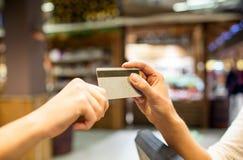 Feche acima das mãos que dão o cartão de crédito na alameda Fotos de Stock Royalty Free