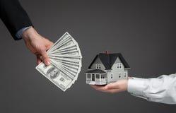 Feche acima das mãos que dão o modelo da casa para o dinheiro Fotografia de Stock