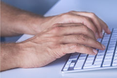 Feche acima das mãos que datilografam no teclado Foto de Stock