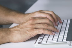 Feche acima das mãos que datilografam no teclado Fotos de Stock