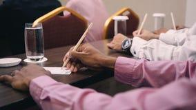 Feche acima das mãos que escrevem na reunião de negócios filme