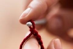 Feche acima das mãos que fazem malha com agulha de crochê imagem de stock