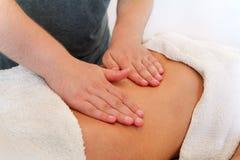 Feche acima das mãos que fazem massagens o abdômen fêmea imagens de stock