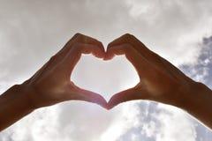 Feche acima das mãos que formam o coração e o céu foto de stock