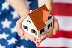 Feche acima das mãos que guardam a casa sobre a bandeira americana Fotografia de Stock