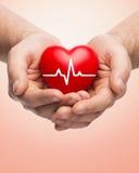 Feche acima das mãos que guardam o coração com cardiograma Fotografia de Stock Royalty Free