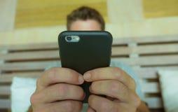 Feche acima das mãos que guardam o telefone celular do quarto do homem novo em casa usando os meios sociais app do Internet em tr imagens de stock